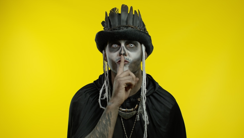 Creepy man with skeleton makeup in top-hat with feathers. Strict guy asking to stay calm, keep silence or secrecy with finger on lips gesture, confidential information. Shh, be quiet. Halloween party | Shutterstock HD Video #1059814667