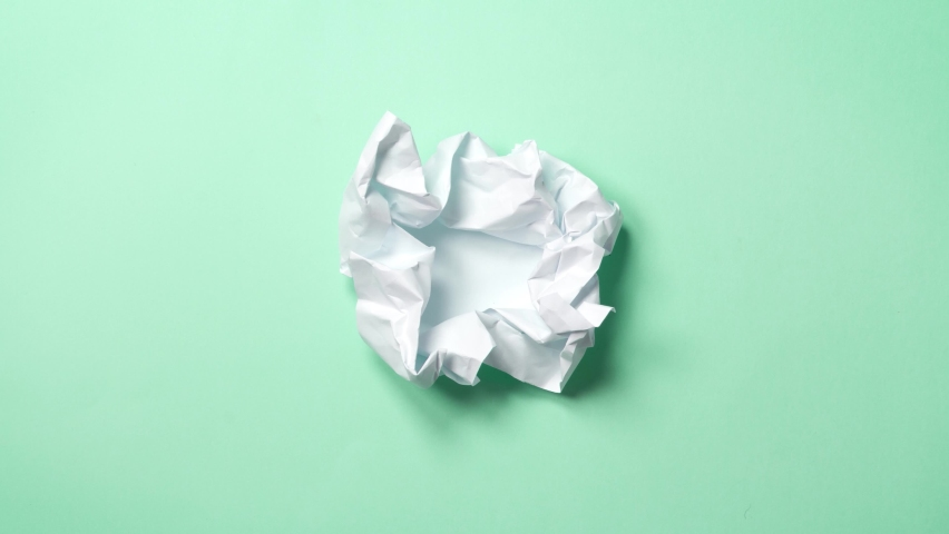 stop motion animation paper wrinkles making a paper ball. Mint green background. A paper ball spreads making a blank sheet and folds again until it disappears. Royalty-Free Stock Footage #1059815936