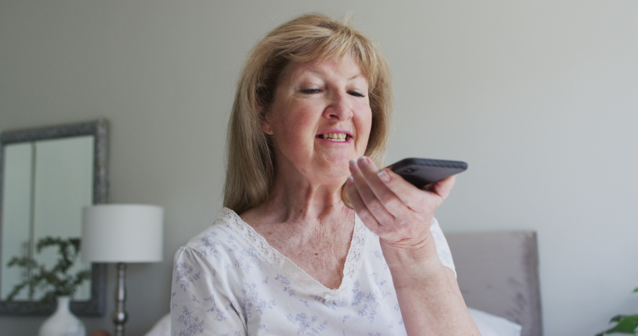 Senior Caucasian woman spending time at home, sitting in her living room talking on a smartphone. Social distancing during Covid 19 Coronavirus quarantine lockdown, slow motion