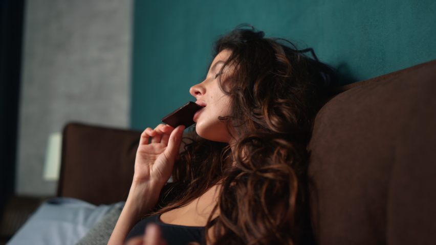 Portrait of sensual woman enjoying chocolate in bed at home. Closeup attractive girl licking fingers with bar of chocolate in hand at bedroom. Sexy model girl eating sweets indoors.