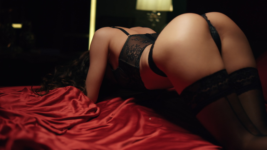 Unknown sexy girl hips arching on red silk sheets in bed. Back view seductive woman buttocks standing on bed in doggy style sexy pose. Hot model girl posing in lace lingerie in dark bedroom.