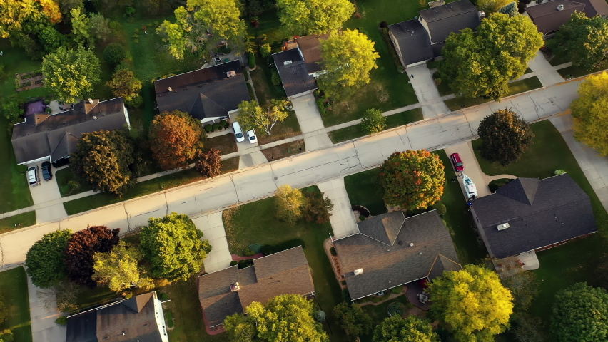 Aerial drone view of American suburban neighborhood. Establishing shot of America's  suburb, street. Residential single family houses, lush greenery. Autumn colors, Fall season, trees with yellow red
