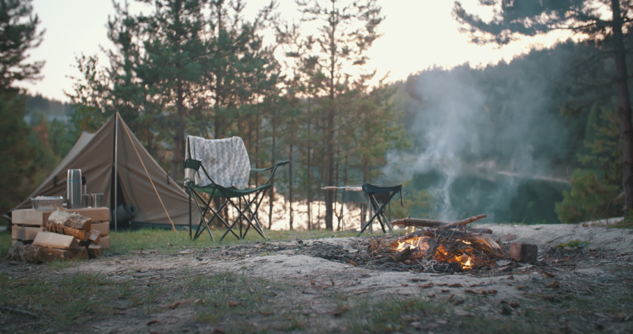 Bonfire burning on beautiful mountain lake shore in tourist camp. Beautiful landscape, campfire, burning wood by tent in summer evening. Active lifestyle, traveling, vacation, hiking, camping concept | Shutterstock HD Video #1059833798