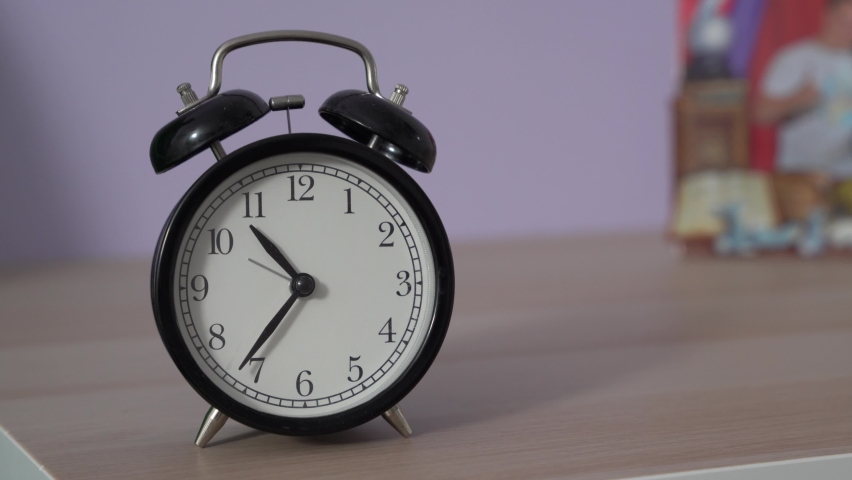The hands of vintage alarm clock quickly move backwards as metaphor for time machine, front view. Daylight saving time. Unexplained mystical phenomena on magical Halloween night Royalty-Free Stock Footage #1059842726