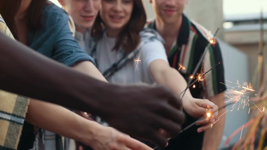 Holding sparklers. Group of young people in casual clothes have a party at rooftop together at daytime.