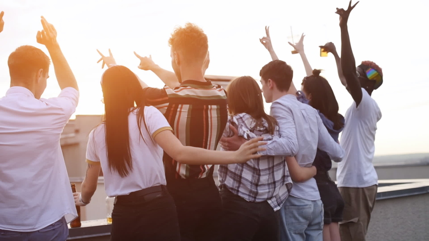 Looking at sundawn together. Group of young people in casual clothes have a party at rooftop together at daytime.
