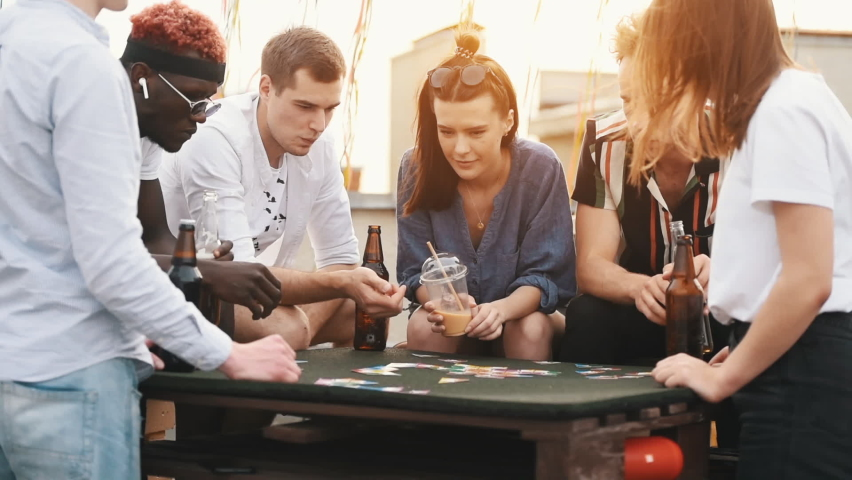 Playing card game and drinking. Group of young people in casual clothes have a party at rooftop together at daytime.