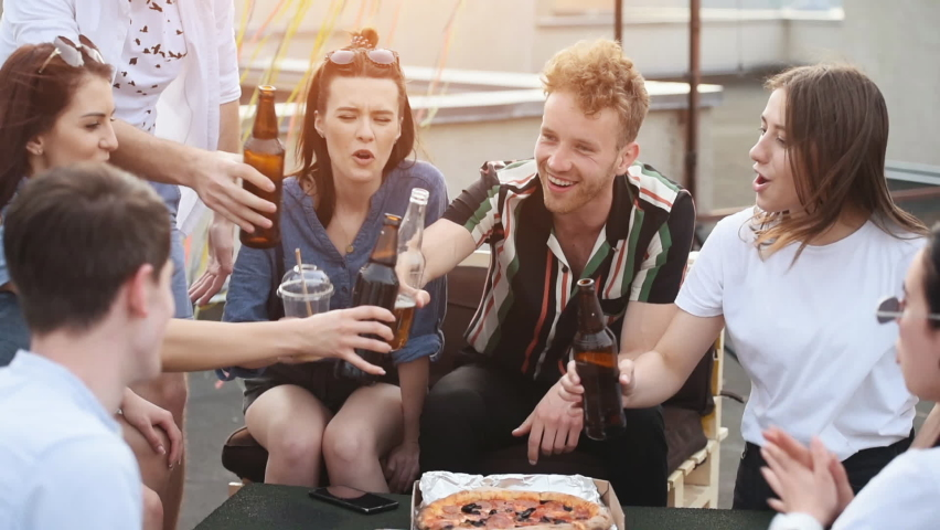 Toasting and drining. Group of young people in casual clothes have a party at rooftop together at daytime.