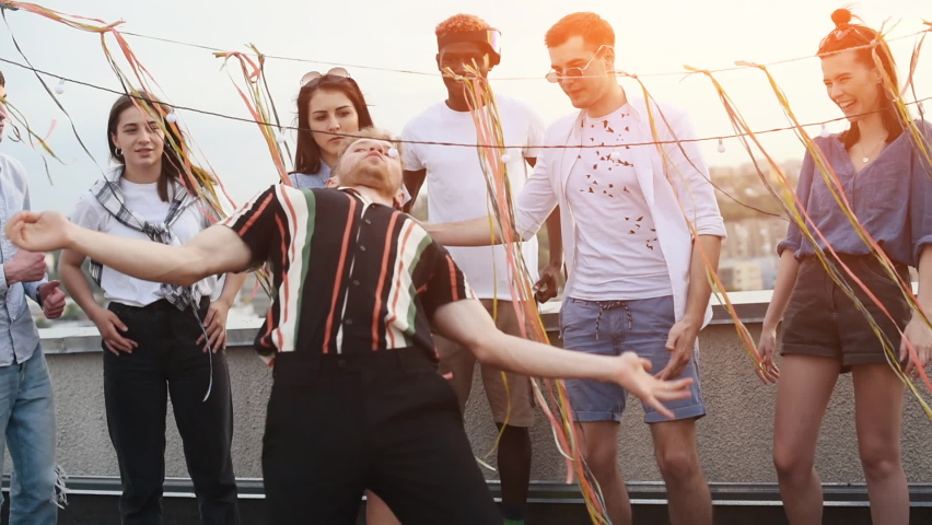 Friends goes under the rope. Group of young people in casual clothes have a party at rooftop together at daytime.