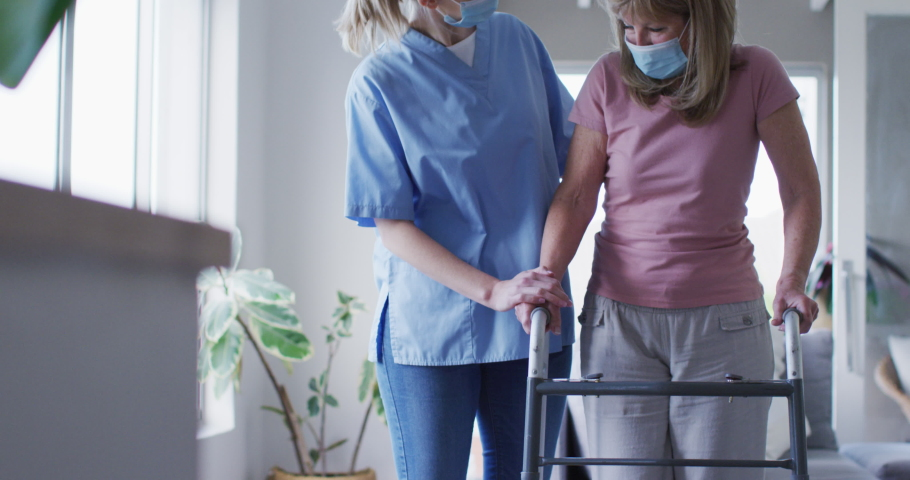 Senior Caucasian woman at home visited by Caucasian female nurse, walking using a walker, nurse wearing face mask. Medical care at home during Covid 19 Coronavirus quarantine, slow motion