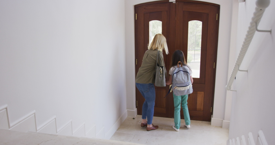 Caucasian woman spending time with her daughter together, going to school leaving their house in slow motion. Social distancing during Covid 19 Coronavirus quarantine lockdown.
