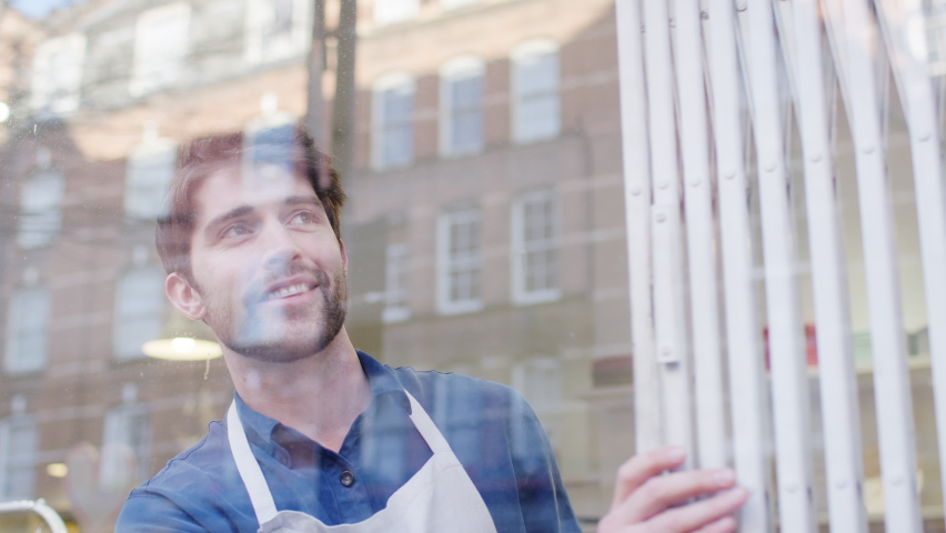 Man running small business pushing back security grill from window and opening shop viewed from outside - shot in slow motion Royalty-Free Stock Footage #1059851573