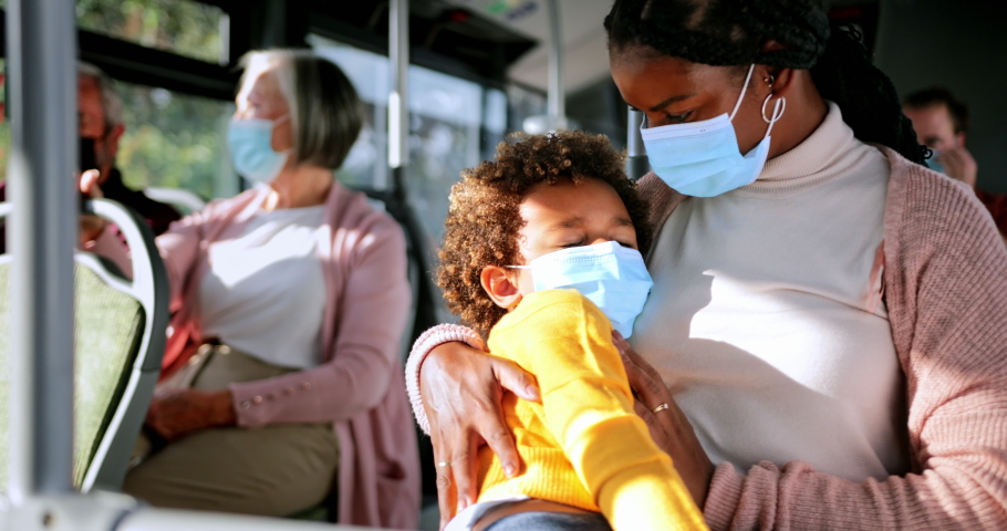 African-american woman holding sleeping boy inside bus wearing covid masks Royalty-Free Stock Footage #1059858092