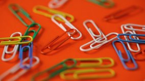 colored paper clips fall on the orange table. school supplies. paper clips close up