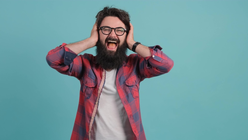 Close up of a young stressed man covering ears with hands, refusing to listen, screaming, shouting, isolated on a turquoise background. | Shutterstock HD Video #1059862190
