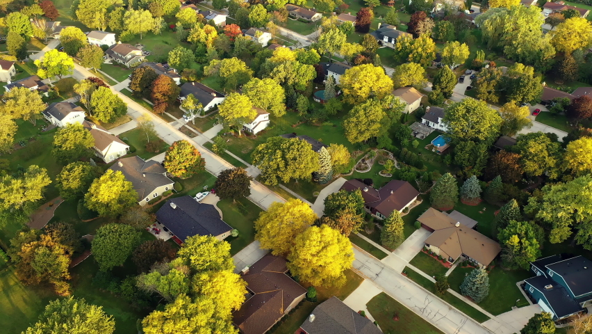 Aerial footage of  an American town  showing typical suburban housing estates with rows of houses, taken on a sunny day using a drone. Establishing shot of typical suburban neighborhood