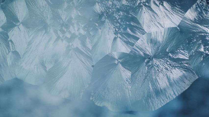 Beautiful freezing ice crystal flowers on window with blue background, macro | Shutterstock HD Video #1059863624