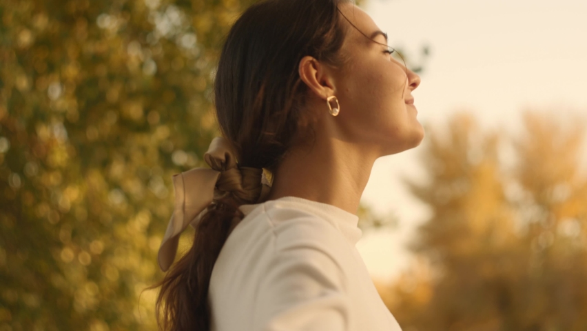 Portrait of an attractive brunette woman walking in the park at fall on a sunny day and smiling. The face of a happy beautiful woman in autumn outdoor. Slow-motion 4k footage