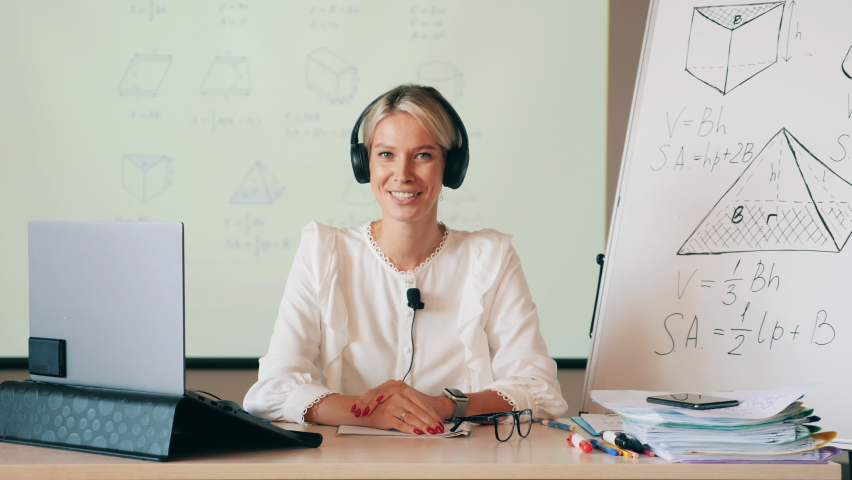A woman in headphones is teaching an online class. Distant studying, remote education, online lesson during lockdown. Royalty-Free Stock Footage #1059870185