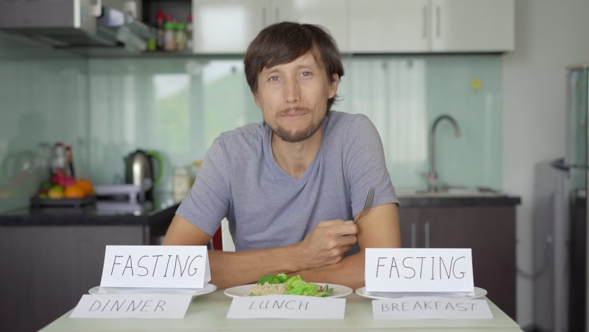 A happy young man eats healthy lunch while signs fasting are on empty plates with signs breakfast and dinner. Interval fasting concept. Skipping meals