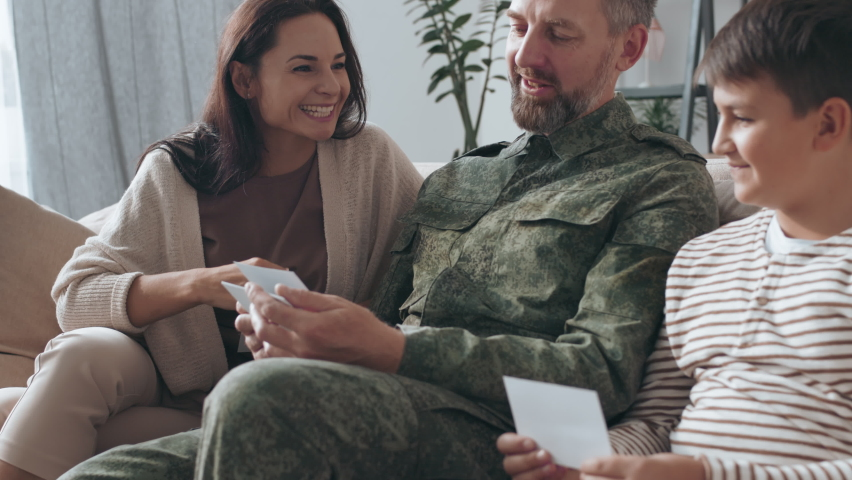 Slowmo medium shot of happy young woman and boy sitting on couch with male army veteran in uniform and listening to him share stories while looking at photos