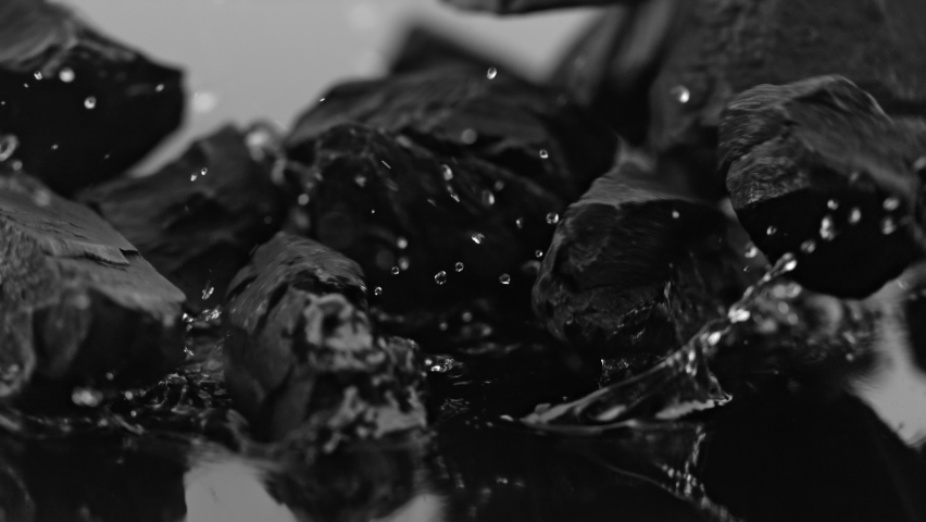 Super Slow Motion Shot of Coal Falling into Water at 1000 fps.