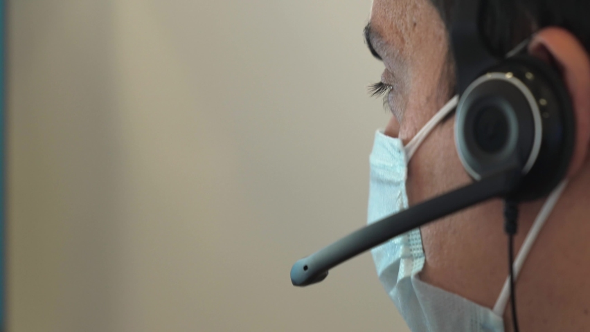 Close-up of a man in a medical mask talking on a headset in an office. Portrait of a male call center operator during a virus outbreak. Business worker answer customer calls during outbreak covid Royalty-Free Stock Footage #1059882110