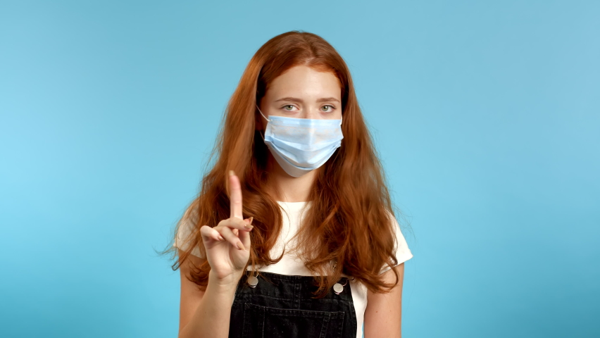 Pretty Woman in medical protective mask disapproving with no finger sign make negation gesture. Denying, Rejecting, Disagree, Portrait of woman on blue background. | Shutterstock HD Video #1059889811