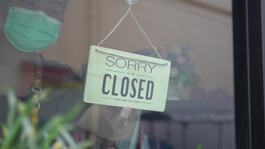 Asian woman wear mask turning Welcome we are open sign on fronton glass door cafe. Reopening activity after COVID-19, ended the lockdown and quarantine. Restarting again and keep forward concept. | Shutterstock HD Video #1059891860