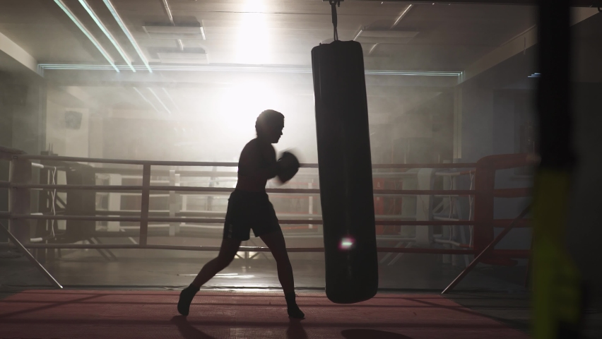 Kickboxing, woman fighter trains his punches, beats a punching bag, training day in the boxing gym, strength fit body, the girl strikes fast. Royalty-Free Stock Footage #1059897722