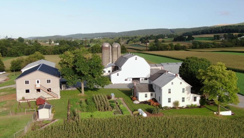 Aerial orbit of Amish farm and buildings, barn, silos, manicured gardens in Lancaster County, Pennsylvania USA. Plain People, Mennonite Community.