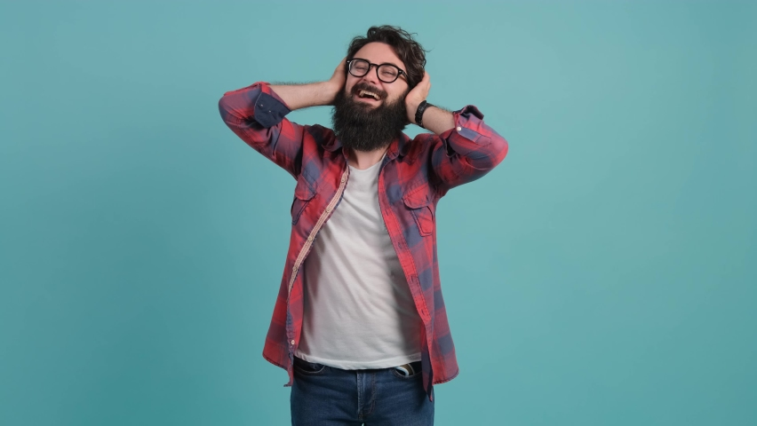 Portrait of a young stressed man covering ears with hands, refusing to listen, screaming, shouting, isolated on a turquoise background. | Shutterstock HD Video #1059922550
