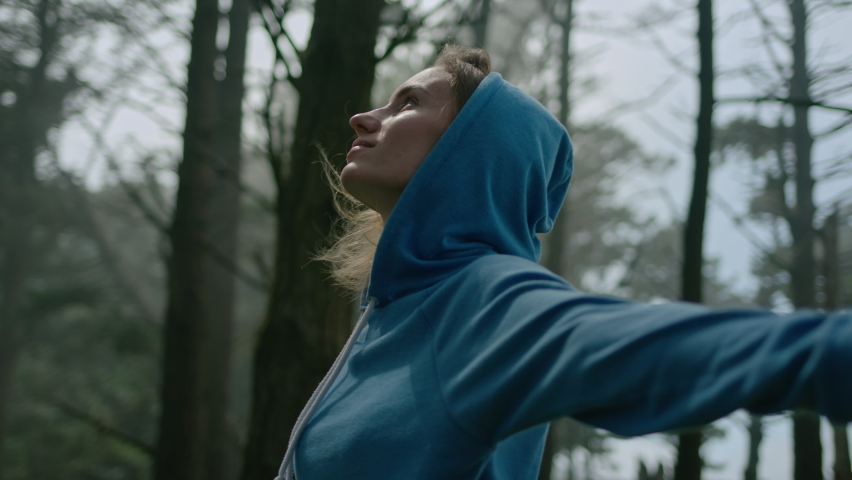 Arc Shot of Young Woman Standing in Forest and Turning around with Her Arms Spread Wide and Eyes Closed. She Enjoys Gentle Breeze, Breathes Deeply and Smiles Subtly. Slow Motion Cinematic Shot Royalty-Free Stock Footage #1059928004