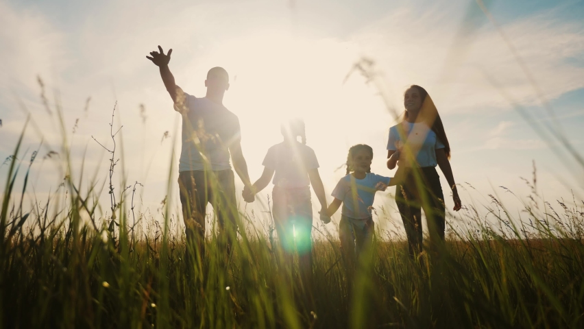 Happy family walking together in the park silhouette. friendly family kid dream concept. lifestyle happy family walking holding hands in the park on the grass at sunset. friendly family dream together