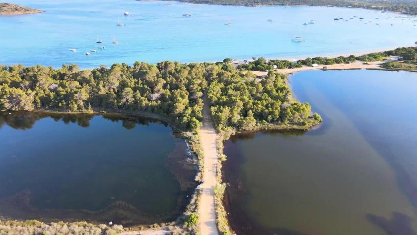 fantastic drone shot of the beautiful sea with a road connecting the beach of Pinarellu to the pond near Porto Vecchio corsica