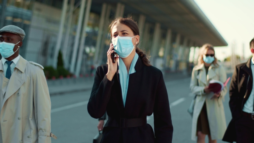 Young businesswoman walking with crowd of office people talking smartphone wearing protective face masks going to work outdoors. Social distancing. Quarantine. Royalty-Free Stock Footage #1059937193