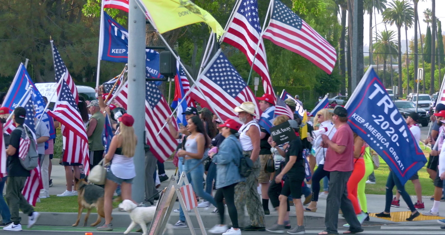 LOS ANGELES, CALIFORNIA, USA - AUGUST 26, 2020: Crowd of President Donald Trump supporters with flags participate in rally in Beverly Hills, Los Angeles, California, 4K