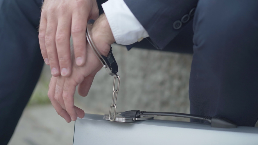 Close-up of male hand chained to attache case with handcuffs. Unrecognizable secret agent with governmental secrecy materials, or symbol of overworked businessman inseparable from work. | Shutterstock HD Video #1059948389