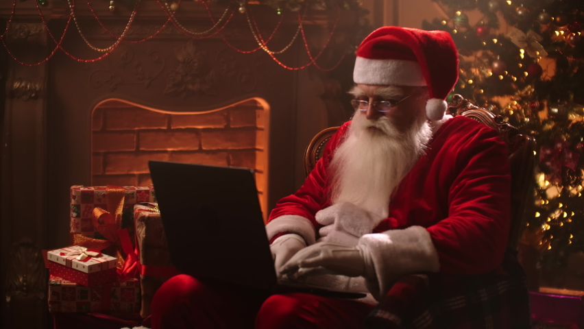 Modern Santa Claus. Cheerful Santa Claus working on laptop and smiling while sitting at his chair with fireplace and Christmas Tree in the background. #1059957197