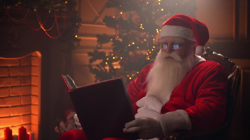 Santa Claus sitting at his room at home near Christmas tree and resting by his fireplace. | Shutterstock HD Video #1059957254