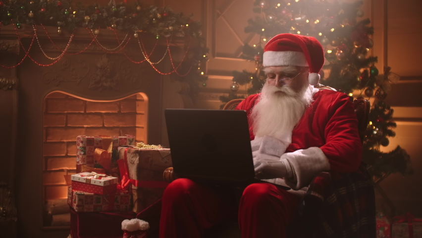 Santa Claus warm atmosphere in living room using laptop. | Shutterstock HD Video #1059957293