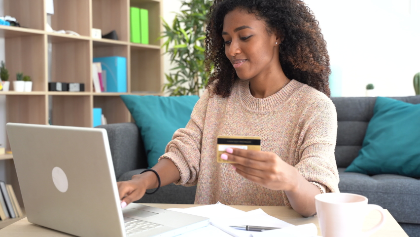 Video about one black home using credit card for online shopping from home, the shot gets slowly closer to the woman Royalty-Free Stock Footage #1059965777