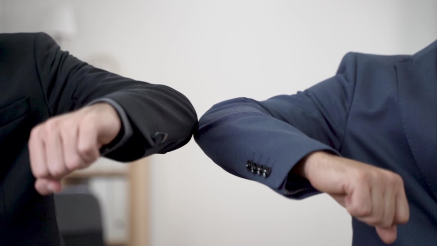 Elbow bumping. A new way of greeting to avoid the spread of coronavirus (COVID-19). Two Businessman bump elbows instead of hug or handshake. New normal. Royalty-Free Stock Footage #1059973805