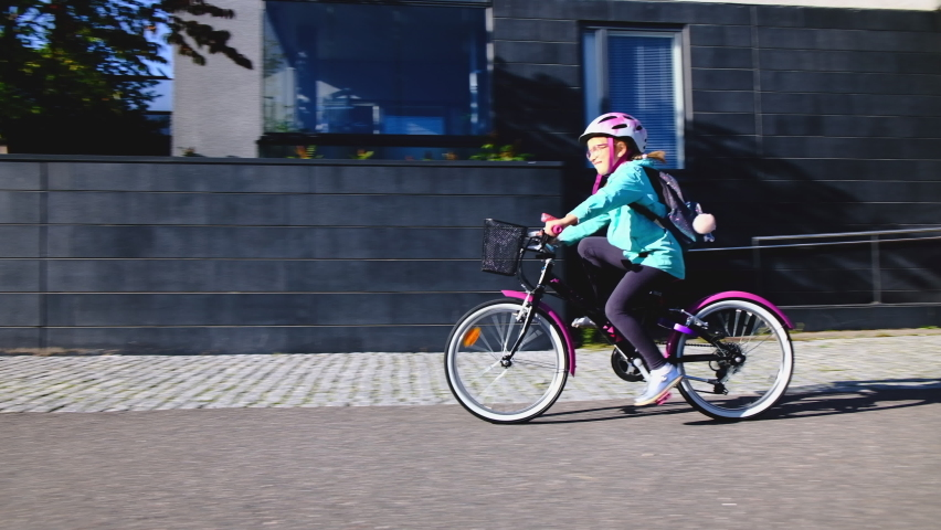 The girl rides the bicycle to school on a sunny morning. | Shutterstock HD Video #1059977003