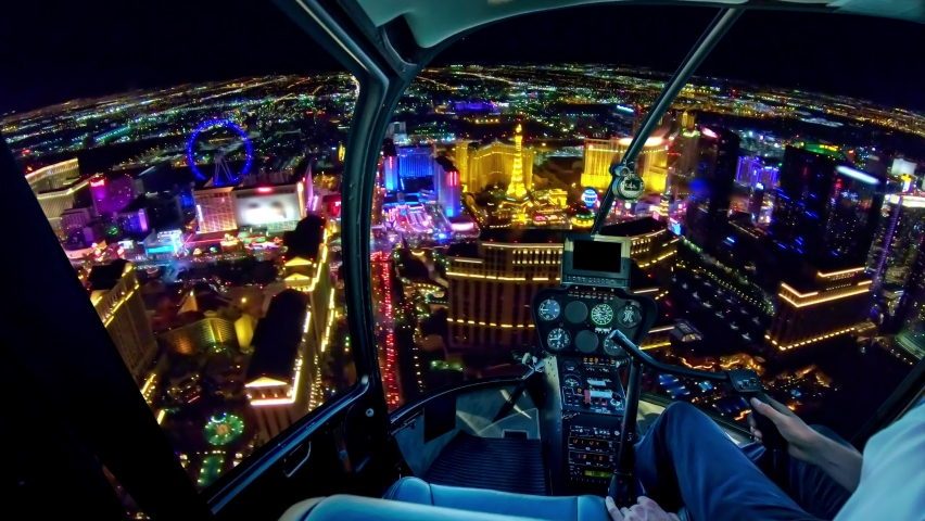 Helicopter interior on Las Vegas buildings and skyscrapers of downtown with illuminated casino hotels at night. Scenic flight above Vegas skyline by night in the Nevada United States of America. | Shutterstock HD Video #1059977813