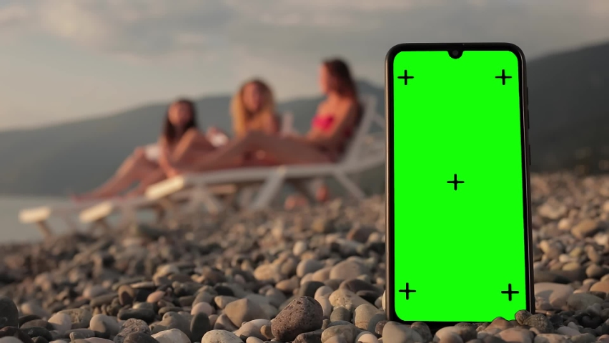 A phone with a green screen and tracking points on the beach, three multi-racial girls in swimsuits lie on sun beds and put on masks on vacation in the background. The chroma key. Isolation. Wear a