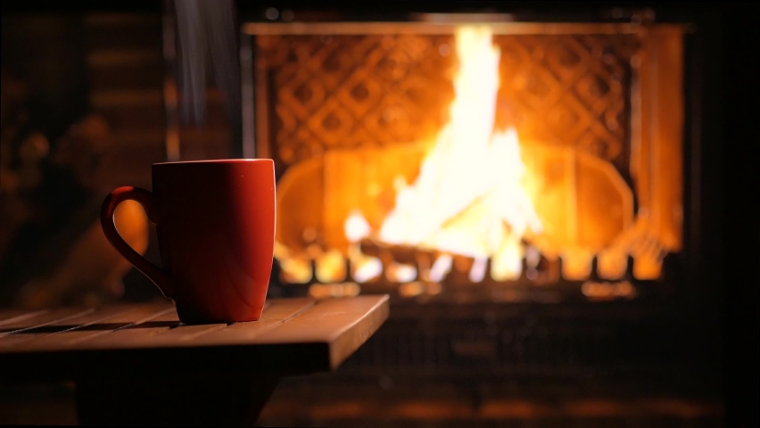 A cup of hot tea in front of the fireplace on a cozy evening. Festive mood	 | Shutterstock HD Video #1059984530