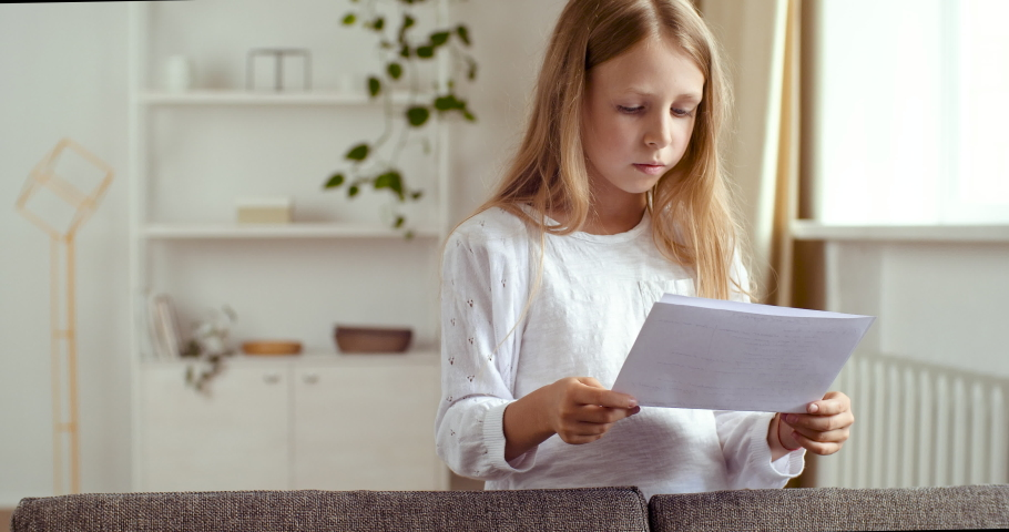 Focused girl of 7-10 years old stands at home reading script of play, preparing for casting for role in school theater. Lady small child repeats rules, learns verse, does homework in room in qurantine | Shutterstock HD Video #1059988529