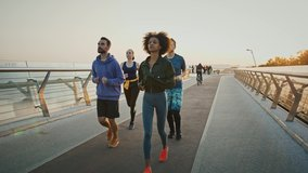 Morning run workout. Group of multiracial people jogging together on sport path in big city, slow motion