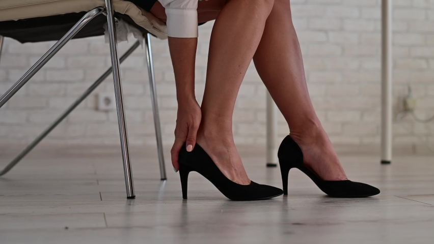 A business woman sits in an office on a chair, takes off her high-heeled shoes and massages her tired feet Royalty-Free Stock Footage #1059992774